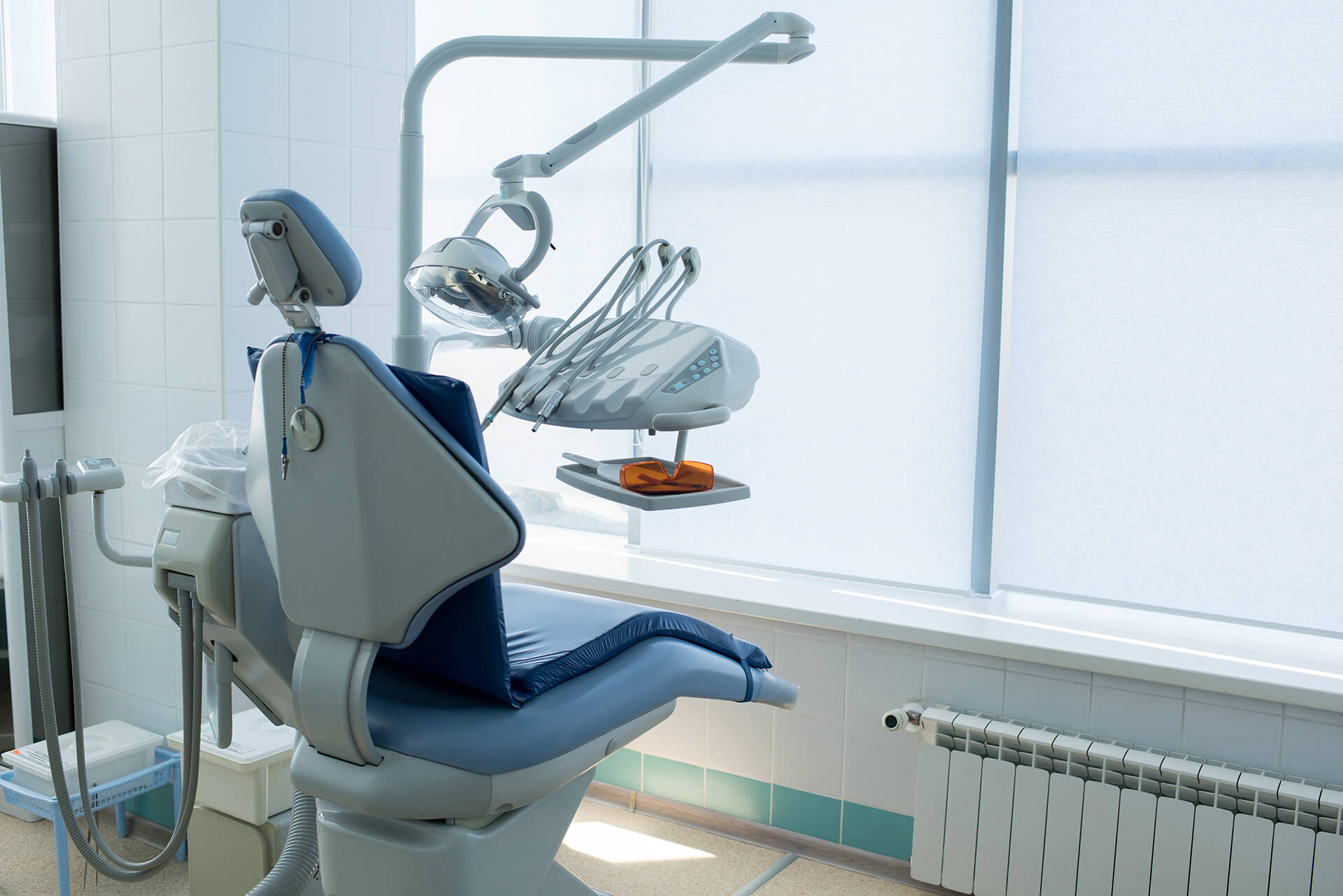 Blue colored seat and working objects of dentist placed in light modern office