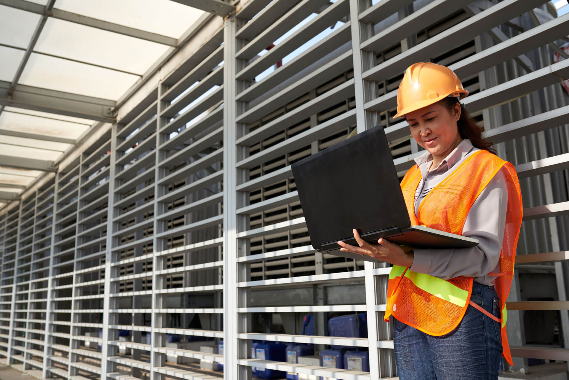 woman looking at laptop with construction safety gear on